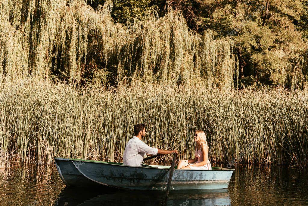 giovane coppia in barca sul fiume vicino boscaglia di carice