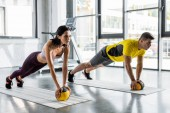 sportsman and sportswoman doing plank with balls in sports center