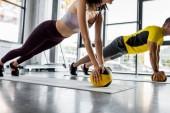 Ausgeschnittene Ansicht von Sportler und Sportlerin beim Planken mit Bällen im Sportzentrum