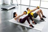 sportovec a sportovkyně dělají křupky s míčky na fitness podložky ve sportovním centru