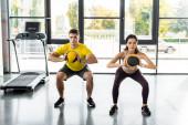 Fényképek sportoló és sportos nő csinál guggolás labdák a sportközpontban