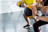 Ausgeschnittene Ansicht von Sportlern und Sportlerinnen beim Kniebeugen mit Bällen im Sportzentrum