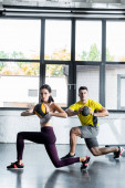Photo sportsman and sportswoman doing lunges with balls in sports center