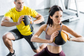 Fotografie sportsman and sportswoman doing lunges with balls in sports center