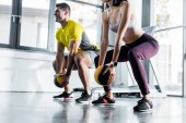 Fotografie sportovec a sportovkyně dělá dřepy s míčky ve sportovním centru