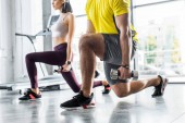 Photo cropped view of sportsman and sportswoman doing lunges with dumbbells in sports center