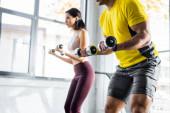 Fotografie oříznutý pohled na sportovce a sportovkyni cvičící s činkami ve sportovním centru
