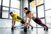 Photo sportsman and sportswoman doing plank on weights in sports center