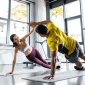 Fotografie sportovec a usmívající se sportovkyně dělá prkno a tleskání na fitness podložky ve sportovním centru