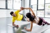 Fényképek mosolygó sportoló és sportos nő csinál deszka és tapsoló fitness szőnyeg a sportközpontban