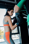sportswoman in boxing gloves working out with sportsman in sports center