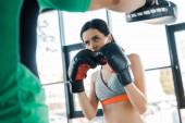 sportovkyně v boxerských rukavicích cvičí se sportovcem ve sportovním centru