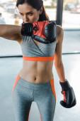 sportovkyně v boxerských rukavicích shlíží dolů do sportovního centra