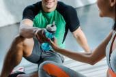 oříznutý pohled na usmívajícího se sportovce dávat sportovní láhev sportovkyně ve sportovním centru