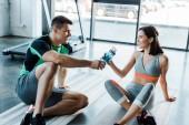 Fotografie usmívající se sportovec dává sportovní láhev sportovkyni ve sportovním centru