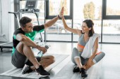 sportsman and sportswoman sitting and giving high five in sports center