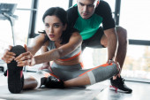 Photo sportswoman stretching and sportsman helping her in sports center