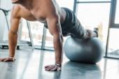 Fotografie ostříhaný pohled pohledného sportovce dělá prkno na fitness míč ve sportovním centru
