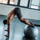 pohledný sportovec cvičit na fitness míč ve sportovním centru