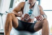 Fotografie Ausgeschnittene Ansicht eines Sportlers, der auf einem Fitnessball sitzt und eine Sportflasche im Sportzentrum hält
