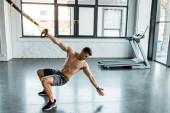 pohledný sportovec cvičit na odpružení trenér ve sportovním centru