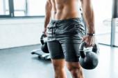 Fotografie oříznutý pohled na sportovce cvičícího s činkami ve sportovním centru
