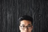 vágott kilátás ázsiai férfi szemüvegben nézi kamera fából készült háttér