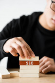 cropped view of seo manager playing with wooden rectangles with lettering seo