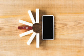 vrchní pohled na dřevěné obdélníky s písmem seo a smartphone s kopírovacím prostorem na stole
