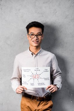 Smiling asian seo manager holding paper with concept words of seo stock vector