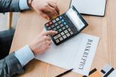 pohled shora na člověka pomocí kalkulačky v blízkosti papíru s bankovními písmeny