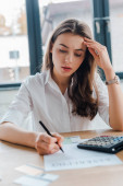 attractive businesswoman signing document with bankruptcy letters