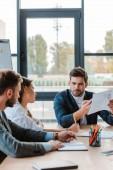 selektivní zaměření podnikatele držící grafy a grafy při sezení v blízkosti spolupracovníků v úřadu