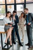 uomini daffari in abbigliamento formale in piedi vicino attraenti colleghi multiculturali in ufficio
