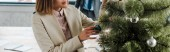 panoramic shot of businesswoman standing near decorated christmas tree in office