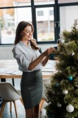 cheerful businesswoman standing near decorated christmas tree in office