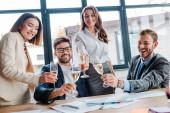 fröhliche multikulturelle Geschäftsfrauen und Geschäftsleute mit Sektgläsern im Büro