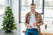 szelektív fókusz vidám férfi holding csésze közelében díszített karácsonyfa