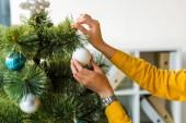 ořezaný pohled na ženu zdobení vánoční stromeček v kanceláři