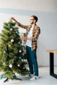 pohledný vousatý muž v brýlích zdobení vánoční strom v kanceláři