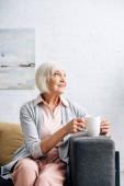 usměvavá starší žena sedící na pohovce a držící šálek v bytě