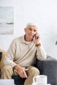usměvavý starší muž sedí na pohovce a mluví na smartphone v bytě