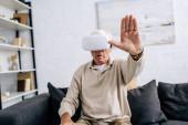 selektivní zaměření seniora ve sluchátkách virtuální reality s nataženou rukou v bytě