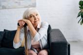 mosolygós idős nő fa bottal nézi kamera a lakásban