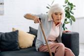 idős nő fa bottal ül kanapén a lakásban
