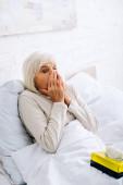 Fotografie attraktive und kranke Seniorin mit geschlossenen Augen, die im Bett niest