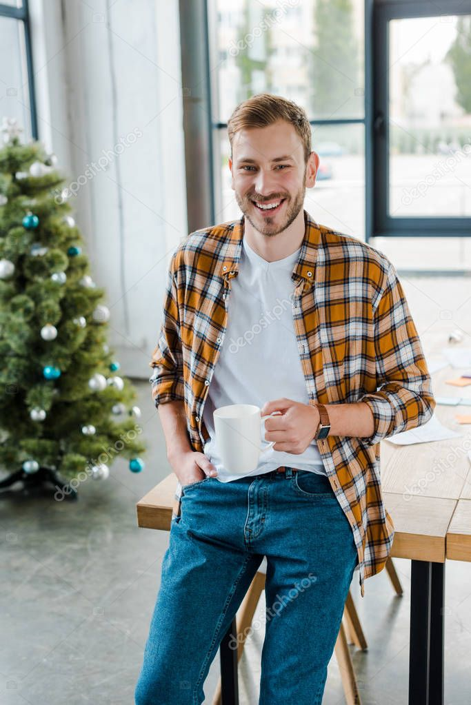 Selective focus of happy man holding cup near decorated christmas tree