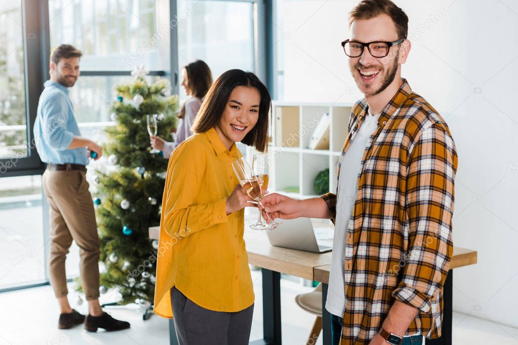 Happy asian woman toasting champagne glasses with man near coworkers in office