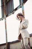 atraktivní stylová žena pózující v béžovém obleku a baretu na střeše