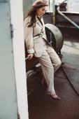 vonzó elegáns lány pózol bézs öltöny és svájci sapka a városi tetőn